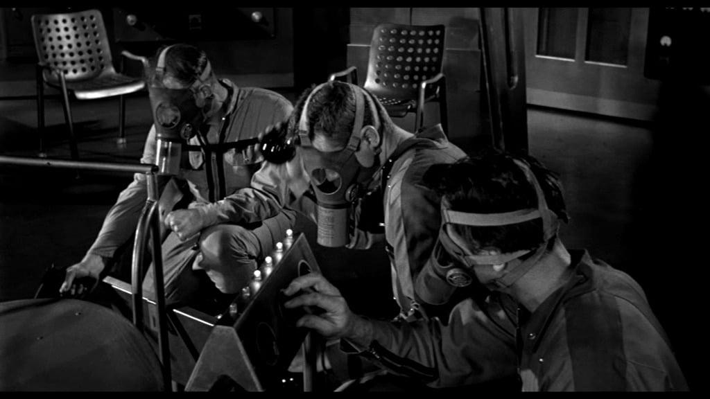 It! Der Schrecken lauert im All - Die Männer hocken mit Gasmasken vor dem Treppenaufgang und warten darauf, dass die Granaten ihre Wirkung tun