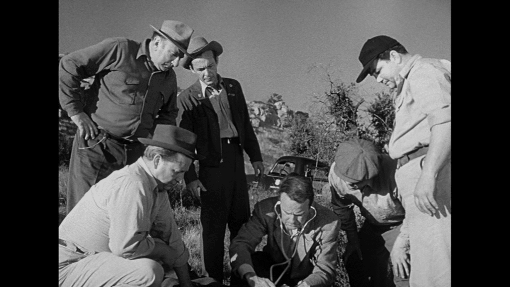 Lew Ayres untersucht in der Wüste das Unfallopfer, neben ihm einige andere Ersthelfer